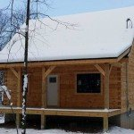 small log cabin covered with snow in the woods, log cabin, log cabin homes, log homes, log cabin kits, Timberhaven, under construction, post and beam, laminated, kiln dried, PA manufacturer