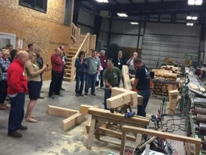 group looking at timber frame joinery, laminated logs, engineered logs, lamination process, log homes, timber frame homes, Timberhaven
