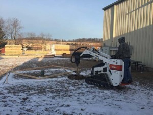 man using a machine to dig footers, product display areas, timber frame display, timber frame pavilion, timber frame outdoor wooden structures