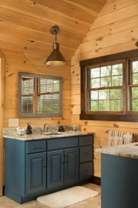log home bathroomw with blue cabinets, log home with stone in the woods, custom log home, Timberhaven, engineered logs, log homes in PA, kiln dried, custom home package