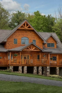 log home with stone in the woods, mountain log home, custom log home, Timberhaven, engineered logs, log homes in PA, kiln dried, custom home package