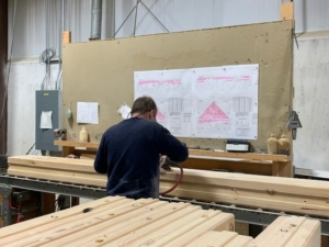 guy sanding logs, logs, white pine, kiln dried, engineered, Timberhaven, Alaskan bound log home